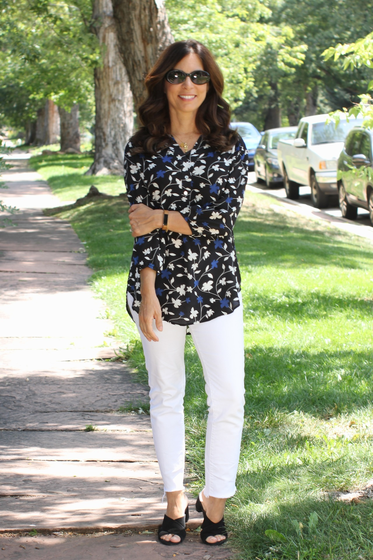 c46c07c77048 Ana from Mrs. American Made keeps cool by wearing a dark floral top with  her white jeans and sandals. I have been reading Mrs. American Made for a  while and ...