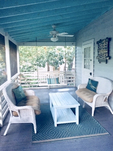 Screened in porch with white wicker furniture and porch swing