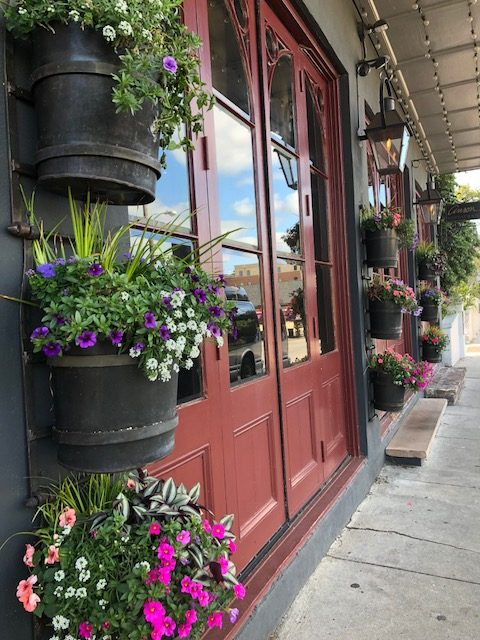 Street in Charleston. Building with Red door surrounded by baskets of flowers