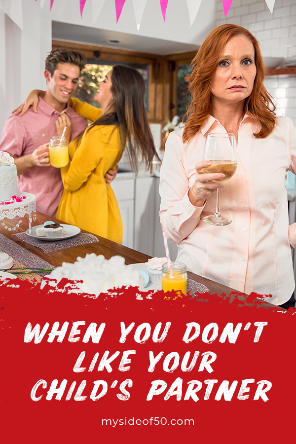 When You Don't Like Your Child's Partner and Other Reasons Their Choice Hurts | Picture of young couple in the kitchen at a party. Mother in foreground with a mad look on her face and holding a cocktail