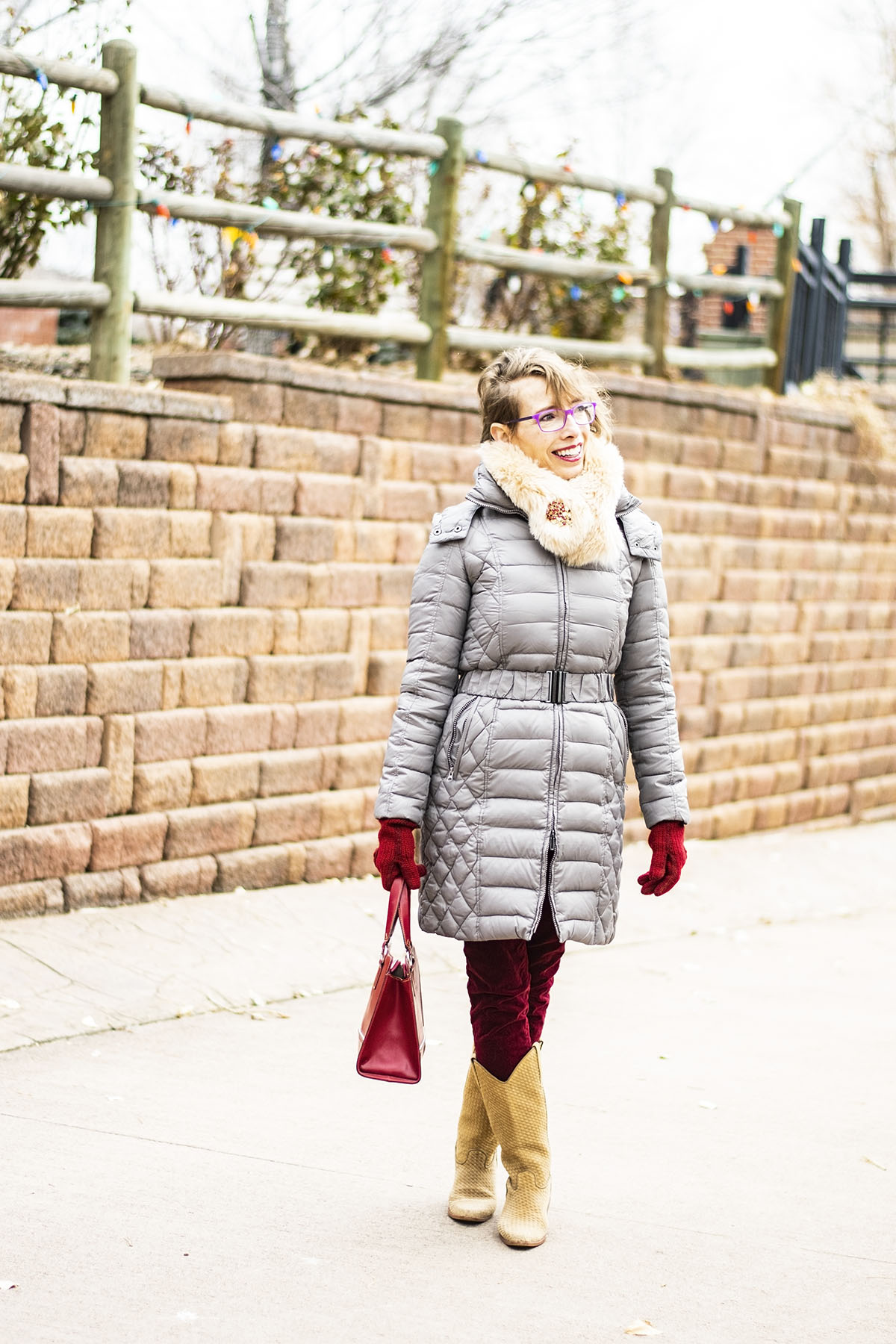 Women's Winter Coats on Sale | Beautiful Coats for Women 50+ | Woman wearing glasses in gray puffer coat with hoot. Also wearing red gloves